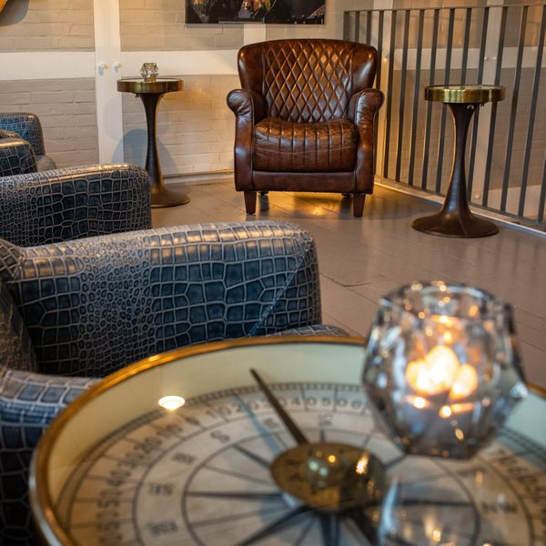 Two leather armchairs and a side table in the shape of a compass in the Captains Lounge.