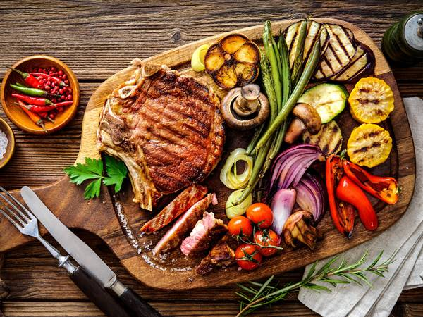 Grilled vegetables, dips and a piece of grilled meat on a wooden board.
