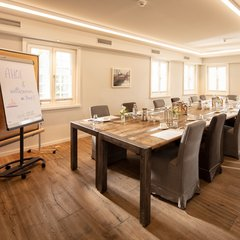The Schiffbrücke conference and event room with several rustic wooden tables arranged as one banquet table in front of a flip chart.