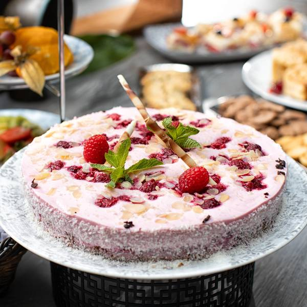 Various buffet dishes with desserts such as raspberry cake with almonds and mint decoration in the atrium of the Hotel Hafen Flensburg.