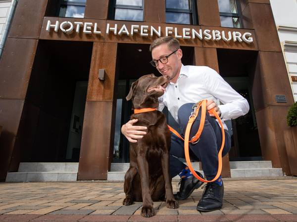 A brown Labrador stands in front of the Hotel Hafen Flensburg, his master kneels beside him and strokes the dog.